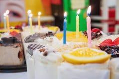 Os bolos frescos do leite e decoraram belamente frutos com as velas do aniversário preparadas para surpreender imagens de stock