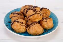 Os bolos frescos dos sopros de creme de Profiteroles encheram-se com o creme de pastelaria imagens de stock