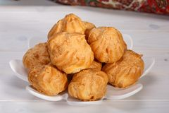 Os bolos frescos dos sopros de creme de Profiteroles encheram-se com o creme de pastelaria dentro imagens de stock