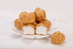 Os bolos frescos dos sopros de creme de Profiteroles encheram-se com o creme de pastelaria dentro fotografia de stock