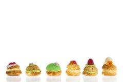 Os bolos ou o profiterole do sopro de creme encheram-se com o chantiliy com fruto e a decoração na linha fotos de stock