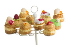 Os bolos ou o profiterole do sopro de creme encheram-se com o chantiliy servido com fruto e decoração fotografia de stock royalty free