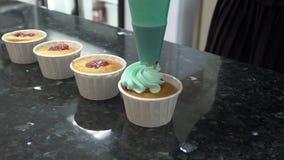 Os bolos prontos são cobertos com uma camada de creme de um saco da pastelaria filme