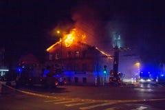 Os bombeiros dirigem o córrego da água em casa ardente construção no inferno flamejante completo, e uma luta do sapador-bombeiro  imagens de stock royalty free