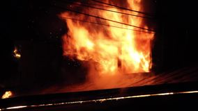 Os bombeiros dirigem o córrego da água em casa ardente construção no inferno flamejante completo, e uma luta do sapador-bombeiro  vídeos de arquivo
