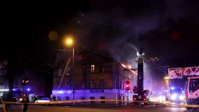 Os bombeiros dirigem o córrego da água em casa ardente construção no inferno flamejante completo, e uma luta do sapador-bombeiro  video estoque