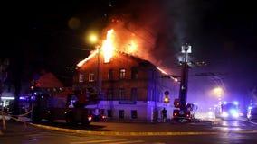 Os bombeiros dirigem o córrego da água em casa ardente construção no inferno flamejante completo, e uma luta do sapador-bombeiro  filme