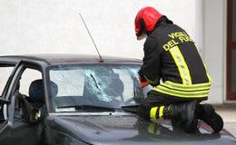 Os bombeiros italianos quebram o para-brisa do carro para liberar o i Imagem de Stock Royalty Free
