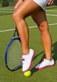 Os bons pés dos esportes estão com a raquete na corte no dia de verão ensolarado Fotografia de Stock