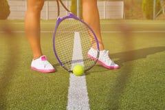 Os bons pés dos esportes estão com a raquete na corte no dia de verão ensolarado Imagem de Stock Royalty Free