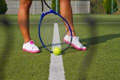 Os bons pés estão com a raquete na corte no dia de verão ensolarado Imagens de Stock