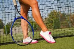 Os bons pés estão com a raquete na corte no dia de verão ensolarado Imagens de Stock Royalty Free