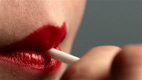 Os bordos fêmeas da boca da mulher 'sexy' sugam um pirulito filme