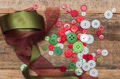 Os botões empilham e laços no fundo de madeira Fotos de Stock Royalty Free