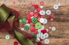 Os botões empilham e laços no fundo de madeira Fotografia de Stock