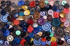 Os botões multi-coloridos velhos dispersaram em um fundo de madeira Imagem de Stock Royalty Free