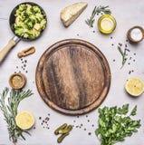 Os brócolis crus em uma frigideira pequena, salsa, óleo, sal, limão, salmouras apresentadas em torno do lugar da placa de corte p Imagens de Stock Royalty Free