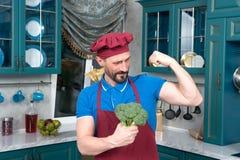 Os brócolis dão o poder equipar o bíceps ou os brócolis escolheram O indivíduo guarda brócolis nas mãos e mostra seu bíceps imagens de stock royalty free