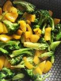 Os brócolis e a pimenta doce em uma bandeja quente, aprontam-se para cozinhar Foto de Stock