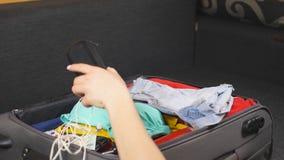 Os braços da embalagem da jovem mulher ensacam com material pessoal para a viagem ou as férias A menina prepara-se para o voo ao  filme