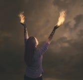 Os braços da mulher no fogo.