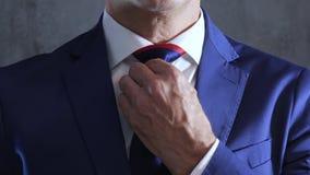 Os braços da pessoa no terno azul endireitam a gravata no pescoço no fundo do muro de cimento cinzento filme