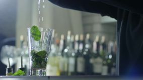 Os braços do barkeeper adicionam o suco fresco no vidro transparente com hortelã das hortaliças e as fatias cimentam o close-up filme
