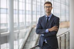 Os braços executivos novos seguros cruzaram o prédio de escritórios moderno da escada rolante da arquitetura Imagem de Stock