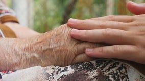 Os braços masculinos novos que consolam um par idoso de mulher adulta entregam exterior Neto e avó que passam o tempo junto video estoque