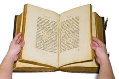 Os braços são viram as páginas do livro velho aberto Fotos de Stock