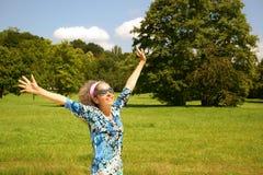 Os braços maduros da mulher esticaram para fora o verão da natureza Fotografia de Stock Royalty Free