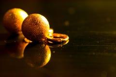 Os brincos brilhantes da bola do ouro refletiram em um fundo lustroso escuro imagens de stock