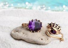 Os brincos da joia do ouro com as gemas na areia encalham o fundo, f macio Imagem de Stock