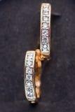 Os brincos do ouro com diamantes fecham-se acima Foto de Stock