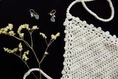 Os brincos fêmeas esmeraldas, um branco fizeram malha a blusa e um ramo em uma tabela preta Foto de Stock Royalty Free
