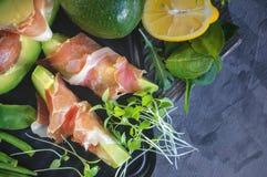 Os brindes deliciosos do abacate e do prosciutto com verde brotaram a mostarda fotografia de stock royalty free