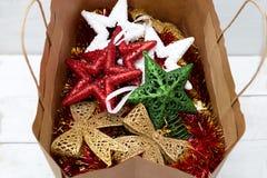Os brinquedos coloridos brilhantes do Natal encontram-se em um saco de compras de papel Fotografia de Stock