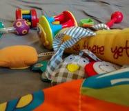Os brinquedos coloridos sortidos do bebê dispersaram na esteira do jogo foto de stock royalty free
