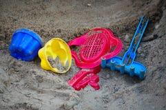 Os brinquedos das crianças na areia Imagens de Stock