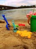 Os brinquedos das crianças na areia contra Imagens de Stock Royalty Free