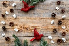 Os brinquedos do pássaro e os cones do pinho para a celebração do ano novo com ramos de árvore da pele no fundo de madeira cobrem Fotografia de Stock Royalty Free