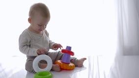 Os brinquedos educacionais, bebê feliz são jogados com brinquedo da pirâmide em casa vídeos de arquivo