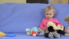 Os brinquedos macios chovem a queda na menina loura bonito que senta-se no sofá O sonho da criança veio verdadeiro filme