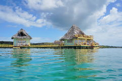 Os bungalows tropicais sobre a água com cobrem com sapê o telhado Foto de Stock