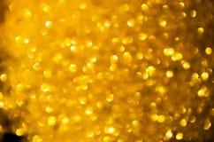 Os círculos amarelos dourados borraram o bokeh do feriado no fundo escuro fotografia de stock