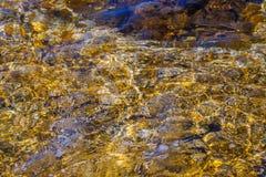 """Os círculos e as reflexões bonitos do ouro e do azul no †da água """"abstraem o fundo imagens de stock"""