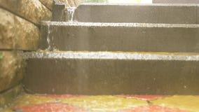 Os córregos da água derramam abaixo das etapas das escadas no parque durante uma chuva de derramamento Movimento lento 4K video estoque