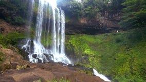 Os córregos espumosos da cachoeira caem do nível elevado no parque video estoque