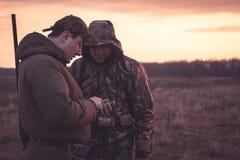 Os caçadores mancham sua posição através do smartphone no campo rual durante a época de caça imagens de stock royalty free