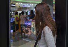 Os cabelos bonitos da senhora cobrem o envio de mensagem de texto da cara com o smartphone dentro do armazém imagens de stock